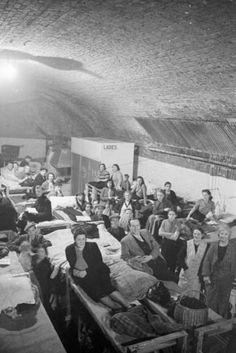 Men  women smile for the camera on  around the bunks that are lined up under the clearly visible roof of a South East London railway arch, probably in November 1940. In the background, the ladies' lavatory can be seen.  It is not possible to identify which of the many railway arches used as air raid shelters during the WW2 is featured in this sequence of photographs, although it is probable that it is at Dockley Road in Bermondsey.
