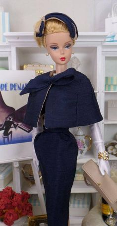 Chic and simple cocktail sheath cut from navy pure silk shantung, fully lined in china silk, and features a slashed empire bodice with contrasting beige china silk, self belt and two tone rosette adornment at the bust line. The skirt has front pleating, back walking slit and button