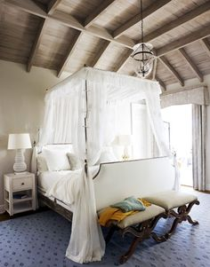 The master bedroom's tall four-poster campaign-style bed soars toward the distressed oak ceiling and gives scale to the room. Breezy bed curtains are Fabricut's Strondak. On bedside tables from Mrs. Howard, Oly's reticulated Pipa lamps add to the overall airiness.   - HouseBeautiful.com