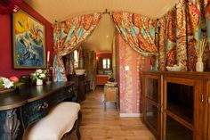 The interior is draped in bright turquoise, orange, and red colors, offset by warm wood and stately decor that could make any guest feel like royalty.   #TinyHouseforUs
