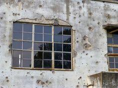 旧日立航空機株式会社立川工場変電所。 .  現地に立っている説明書きによると、 戦争中の、 機銃掃射や爆弾の炸裂によって、 このような凄まじい姿になったのだそうです。 .  さらに、 戦後も、ほとんど修理の手を加えることなく、 1993年(平成5年)12月まで、 変電所として、 変わらず、使われ続けていた、 というから、びっくりです。 .  今では、このあたり、 「平和広場」という、 なんか、わかったようなわからないような、 曖昧な通称になっているみたい。 .  元々、何の変哲もない、この建物。 ...