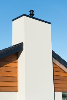 A clean lined plaster over brick exterior is enhanced all the more by stand out Cedar weatherboard features.