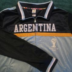 """2014 FIFA Team Argentina World Cup Soccer Jacket Here we have a team Argentina official World Cup Soccer warm up jacket. Light and dark blue. Knit collar and cuffs. 2 side pockets, zip up, inside is a light fleece. In very good condition with only gentle wear. With garment laying flat measures as follows: Chest 27"""" Shoulders 21"""" Arm Pit to Bottom Hem 18"""" Shoulders to Bottom Hem 27"""" Waist 22"""" Sleeve 27"""" FIFA World Cup Jackets & Coats"""