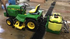 John Deere 318 garden tractor with boom sprayer mounted on 3-point hitch