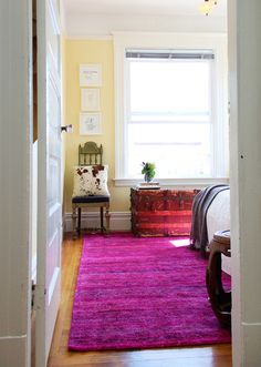 pink rug balanced with dark wood, masculine pillow and travel trunk