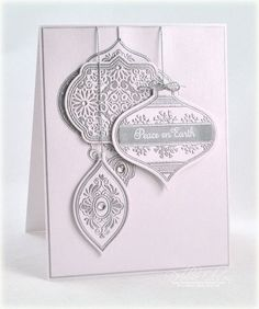 Noel Christmas Ornaments set and heat-embossed several ornaments in detail silver embossing powder after stamping them with Versamark ink. I used the Spellbinders 2011 and 2012 Heirloom Ornaments die template sets to cut two of the ornaments. The largest