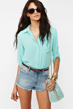 Super cute mint chiffon blouse featuring a button-down front and chest pocket. Button tab at sleeves, oversized fit. Looks perfect paired with circle shades and cutoffs!