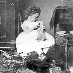 Antique photo of a precious little girl who appears to be feeding her doll, circa 1870.
