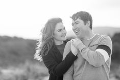 a couple smiling posing for a photoshoot wearing black coat shoulder length wavy hair and a mens grey jumper Wavy Hair, Red Hair, Ireland Beach, Catch A Flight, I Respect You, Wind And Rain, Donegal, Shoulder Length, Engagement Shoots