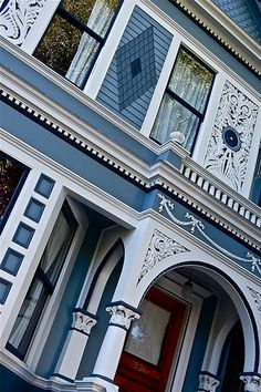 Up close view of the beautifully detailed trim of a blue Victorian house