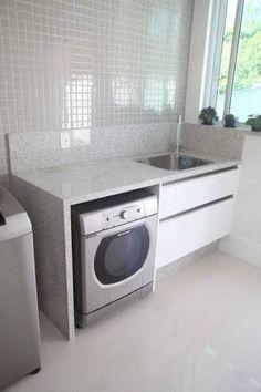 Bancada cor Branco Itaúna com frontão 20cm, interrompida por fogão de piso, sobre máquina lava-roupas e tanque de embutir com armário embaixo.