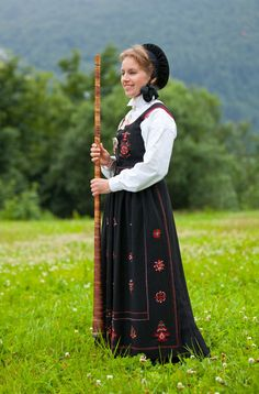 """""""This bunad from Hjørundfjord has a pretty black hat with silk ribbons tied under the chin. The birch-bark horn, was very popular as an """"accessorie"""" on photos taken in the early 20th century. In real life, it was used to call the cows back from the pasture to the barn."""""""