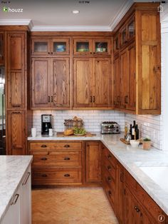 Rich oiled wood shaker cabinets with white tile backsplash and marble countertop
