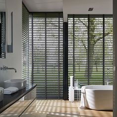 Bathe a bathroom in natural light and the dramatic light controlling style of Parkland™ Genuine Woods blinds. ♦ Hunter Douglas window treatments