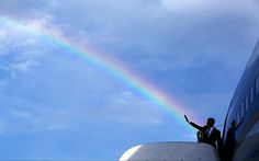 President Barack Obama's wave aligns with a rainbow as he boards Air Force One at Norman Manley International Airport before departing from Kingston, Jamaica, on April 9, 2015.