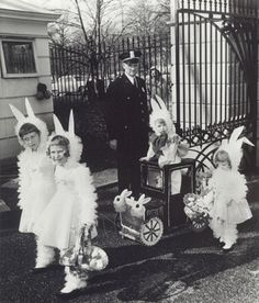 Vintage Easter photo of children dressed up,carrying Easter baskets, and one child in a Bunny Cart.