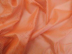 Couro Metalizado Tela, loja online de tecidos (Laranja). Couro ecológico com efeito metalizado suave. Possui vazados circulares, seguindo o padrão de uma tela. Tecido leve e maleável, ideal para peças que exijam certa flexibilidade, mas não para peças fluidas.  Sugestão para confeccionar: Saias, shorts, jaquetas, detalhes em peças, vestidos tubinho, entre outros.