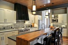"""Gorgeous gray tile (12""""x12"""" cut into 2'x12"""" for dramatic effect), white cabinets and slate gray solid surface counters.  Fir wood raised bar sealed for normal wear and tear.  Transitional Kitchen by Clinkston Architects"""