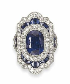 A SAPPHIRE AND DIAMOND RING   Centering upon a collet-set cushion-shaped sapphire in a circular-cut diamond frame, to the shield-shaped calibré-cut sapphire and circular-cut diamond surround and shoulders, mounted in platinum. Art Deco or Art Deco style