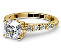 Ten round cut diamonds are prong set in this yellow gold diamond engagement ring setting, accenting your choice of center diamond.