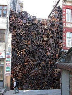"""1550 Chairs Stacked Between Two City Buildings"" is an installation by Doris Salcedo at Istanbul Biennial. In 2002, Salcedo placed 280 chairs at the Palace of Justice in Bogotá ""to pay homage to those killed here in a failed guerrilla coup seventeen years earlier."" In 2003, she filled the Istanbul Biennial space between two buildings with 1,550 chairs ""evoking the masses of faceless migrants who underpin our globalised economy.""    Salcedo's work provokes many questions after a firs"