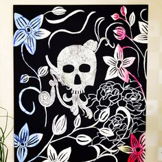 Scull with diamonds, two coloured lillies and silver roses at black background.