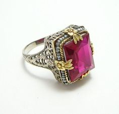 Rare 14k White Yellow Gold Antique Art Deco Red Ruby Pearl Filigree Ring.  Circa1920, unsigned (probably Belais Brothers). Rectangular emerald cut glass ruby stone and imitation seed pearls are set in a two toned white and yellow gold filigree mounting.