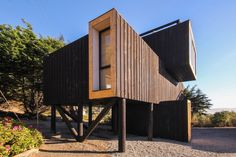 Stacked and rotated black volumes set on stilts make up Chilean seaside house