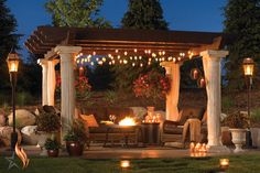Pergola over an outdoor gas fire glass pit with hanging lights