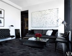 In the living room, painted in Ralph Lauren Pocket Watch White, an artwork by Rodney Dickson hangs above a custom-made sofa clad in a Pollack velvet; the floor lamp is by Arredoluce, and the fox-fur pillows and calfskin rug are by J. Mendel.
