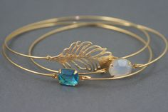 Feather and peacock blue jewel bracelet stack.