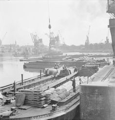 """1944  Regent's Canal, London, UK.                                      """"A busy scene at Regent's Canal Dock in London, the southern terminus of the Grand Union Canal. In the foreground is a large barge, which according to the original caption, unlike canal boats """"can only navigate as far as Berkhampsted"""" and """"carry a great deal of timber up the canal"""". iwm.org.uk"""