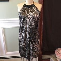 Sexy Animal Print Backless Mini Dress sz L RAWRRRR!!! Bring out your wild side in this Joyce Leslie satin animal print backless minidress! Marked a sz large, but appropriate for a size 6 or 8 medium. Worn and laundered one time. Fraying on one of the ties (see pic). 100% polyester for easy washing. Joyce Leslie Dresses Mini