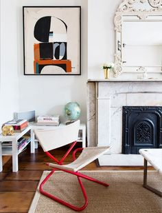 Living room with a marble fireplace, a large mirror, and a structural armchair