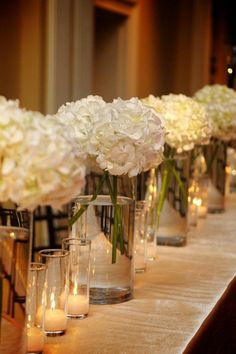 I love this look for table arrangements. I like the glass vases, hydrangeas, and even the candles in the glass vases.