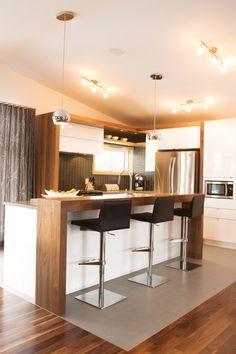 Cuisine 2 tons. Les armoires de cuisine ont été réalisée en thermoplastique blanc lustré avec une insertion de placage de noyer. Comptoir de quartz.