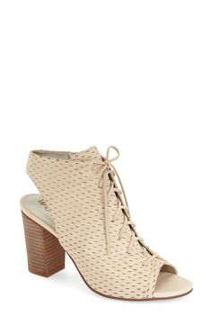 Small perforations define these open toe booties that lace up.