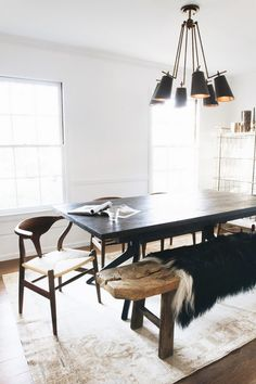Scandinavian inspired dining space with a black dining table, a reclaimed wooden bench, a fur throw, and a black chandelier