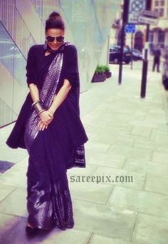 Neha dhupia street style in Satya paul saree. Black saree, silver stripes border and black blouse completed her look.