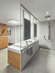 Sleek and modern bathroom design ! This super-modern shower steps away from everything traditional. The vanity's glass backsplash defines the entire space, separating the vanity area from the adjacent shower. With mirrors on one side and towel hooks on the other, the single piece of glass manages to serve both spaces effortlessly.