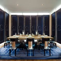 Large dining table with metal base and wooden top dominates the interior of this modern dining room designed by David Collins