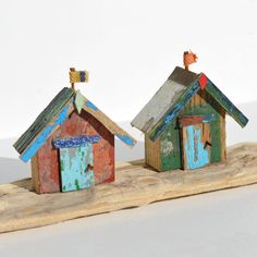 Two characterful and colourful driftwood beach huts on a driftwood. Created from pieces of driftwood, bits of old boat, rusty nails and other beach finds.