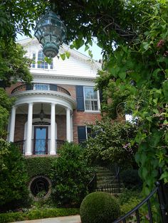 Pillars, stairs, ivy, landscaping, hanging lantern, red brick with black shutters, monogrammed wrought iron grate set in brick