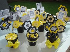 Bee Party- Centerpieces. Scrapbook & cardstock Paper flowers, black & white pics of the girls throughout the year, various ribbon & trim, and these buckets are from Target's dollar section.  (PS if you are a novice like me, don't forget to weigh these down if they'll be outside. I used nice clean SANDBOX sand, which held the floral wire up nicely! i then topped it with a slice of floral foam and tissue paper) eb
