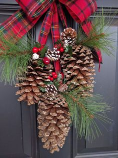 Welcome this winter season with this classic pine cone door swag! Made with 3 JUMBO pine cones adorned with faux green pine and clusters of red berries and greenery hanging from festive plaid flannel ribbon. The pine cones rang in size between 6 - 8 inches in length. The overall length of swag measures approximately 22 inches. Ive included a loop behind the bow for easy hanging. This swag is perfect for decorating indoors and out! Check out all of our Christmas Decor! https://www.et...