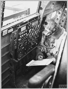 Original wartime caption: For story see CH.12466 Picture (issued 1944) shows - Still grounded, but working as closely as possible to actual flying conditions and wearing oxygen mask and flying kit, a flight engineer cadet reads off his instrument panel and makes a log report. Lancaster Bomber, Oxygen Mask, Maximum Effort, Modern History, Royal Air Force, Radios, Caption, Ww2, Airplane