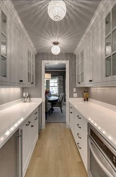 Galley style butler's pantry features a gray ceiling dotted with crystal beaded flush mounts illuminating white cabinets fitted with a stainless steel mini fridge situated across from a pull out microwave drawer.