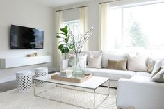 Beautiful living room features a white sectional lined with pale pink velvet pillows as well as yellow and gray ikat pillows in Bansuri Fabric paired with a white marble top box frame coffee table  and white trellis stools atop a cream diamond pattern rug.