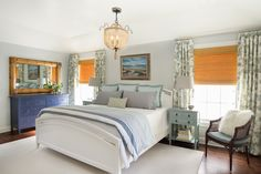 Eclectic bedroom with a  bamboo mirror, natural Roman shades and a coastal chandelier. Two Hands Interiors