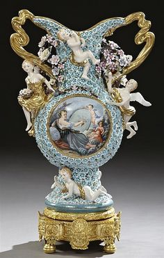 "Large Meissen Style Porcelain Handled Vase, 20th c., with integral swirling gilt porcelain handles, with relief putti and overall ""schneeballen"" flowers, the sides with reserves of putti and the muses of art and literature, on a putti decorated socle support to a shaped lobed relief decorated gilt bronze base, H.- 29 in., W.- 16 1/2 in., D.- 9 3/4 in."
